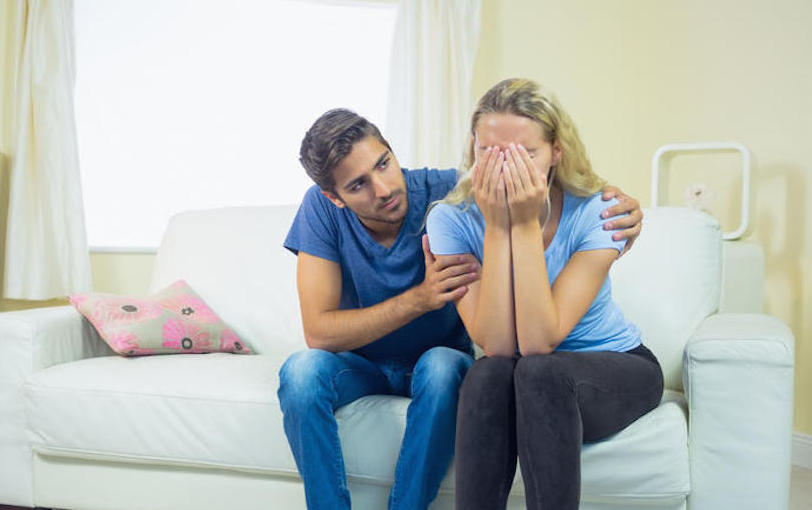 Unhappy crying woman sitting on couch being consoled by her boyfriend
